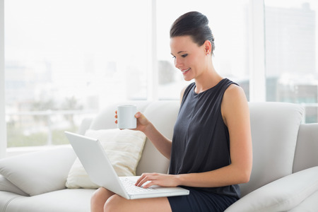 Beautiful well dressed young woman using laptop while having coffee on sofa at bright home photo