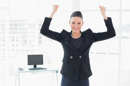 clenching fists: Portrait of an elegant and happy businesswoman clenching fists in a bright office