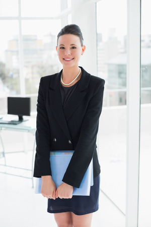 Portrait of an elegant businesswoman standing with folder in office photo