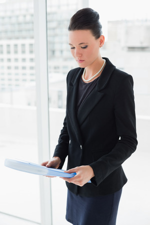 Young elegant businesswoman with folder standing against office glass wall photo