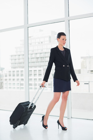 Full length of an elegant businesswoman in suit businesswoman pulling suitcase