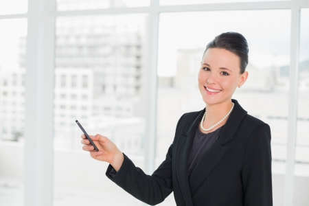 Portrait of a smiling young elegant businesswoman looking at cellphone in a bright office photo