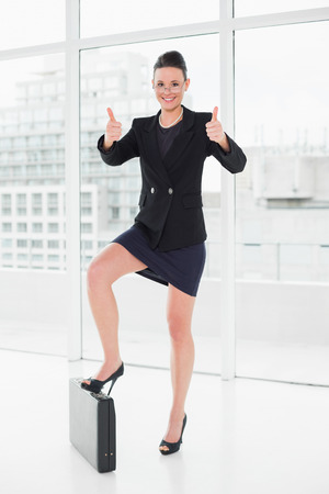 Full length portrait of an elegant businesswoman in suit with briefcase gesturing thumbs up photo