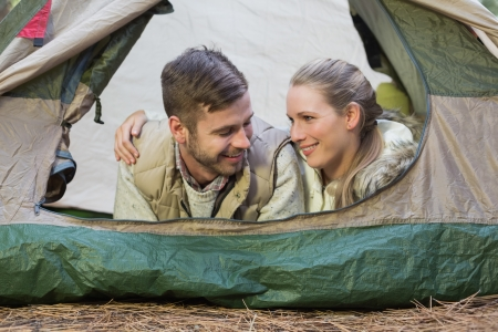 adventuring: Close up of a smiling couple lying in tent after a hike
