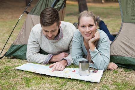 Young couple lying in tent with a map in the wilderness photo