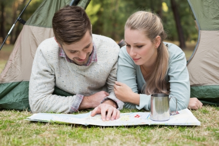 Young couple lying in tent and reading a map in the wilderness photo