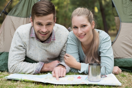 Portrait of a smiling young couple lying in tent with a map in the wilderness photo