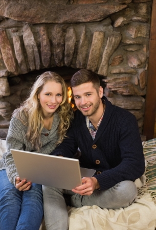 Portrait of a lovely young couple using laptop in front of lit fireplace photo