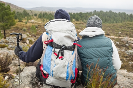 trekking pole: Rear view of a couple with backpack and trekking pole looking at view while on a hike