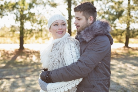 Side view of a loving young couple looking at each other in winter clothing in the woods photo