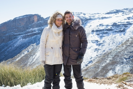 Portrait of a smiling young couple in fur hood jackets against snowed mountain range photo