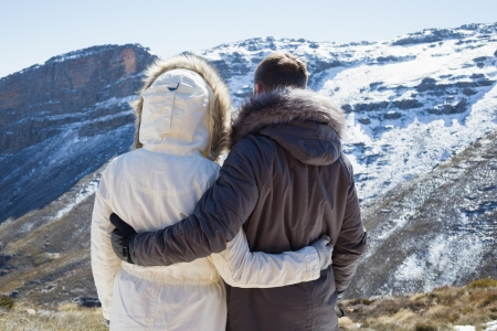 Rear view of a loving couple in fur hood jackets looking at snowed mountain range photo