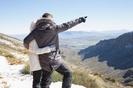 Rear view of a loving couple in jackets looking at mountain range photo