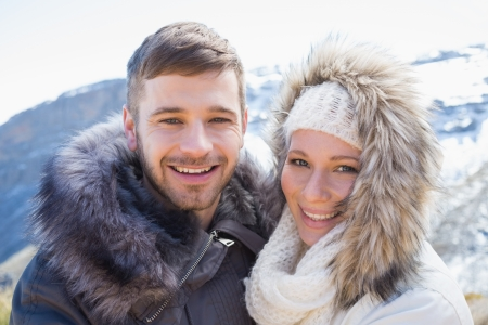 Close up portrait of a loving couple in jackets in front of snowed mountain range photo