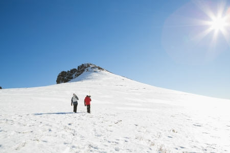 ski walking: Rear view of a couple with ski boards walking on snow covered landscape on a sunny day