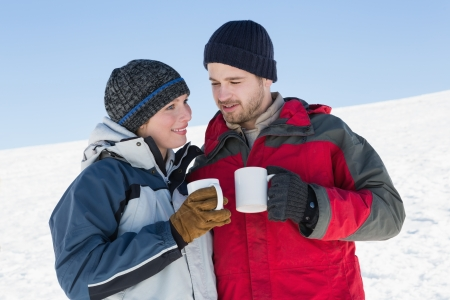 Smiling young couple in warm clothing with coffee cups standing on snow covered landscape photo