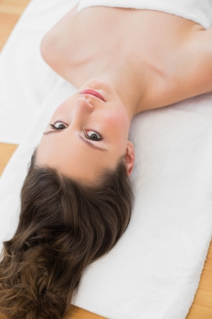 Portrait of a young brunette lying on massage table in beauty salon photo