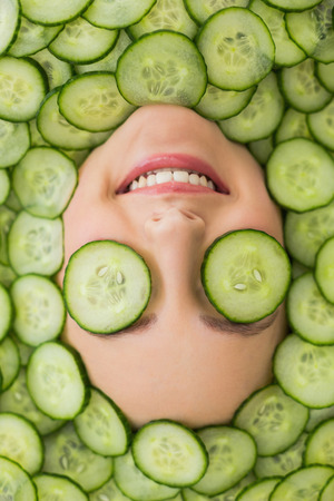 Close up of a young beautiful woman with facial mask of cucumber slices on her face at spa salon Reklamní fotografie