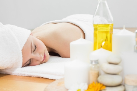 therapeutical: Beautiful young woman resting with oil bottle in foreground at beauty spa