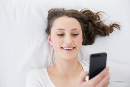 High angle view of a young brunette looking at mobile phone in bed at home photo