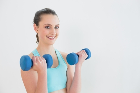 Portrait of a smiling young woman with dumbbells against wall at fitness studio photo