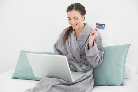 Casual young woman in bathrobe doing online shopping through laptop and credit card in bed photo