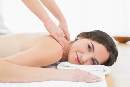 Portrait of a smiling beautiful woman enjoying shoulder massage at beauty spa photo