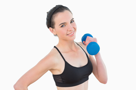 Portrait of a smiling young woman with dumbbell against white background photo