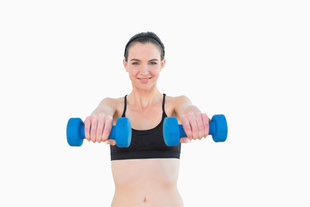 Portrait of a smiling young woman with dumbbells against white background photo