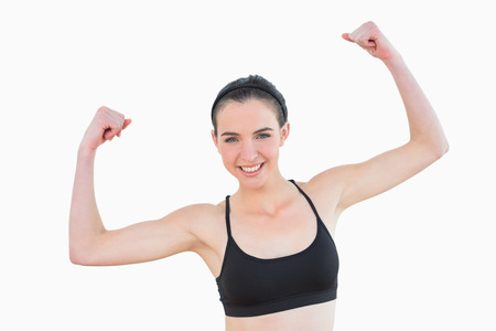 clenching fists: Portrait of a sporty fit young woman clenching fists against white background