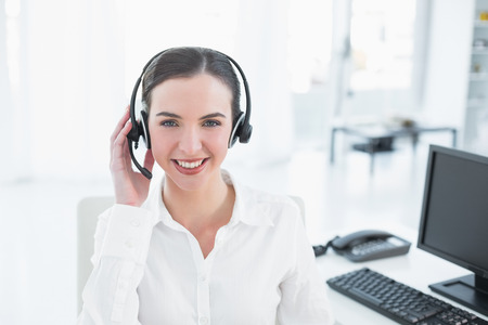 Portrait of a smiling young businesswoman wearing headset by computer in office photo