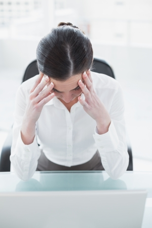 Young businesswoman suffering from headache in front of laptop at office desk photo