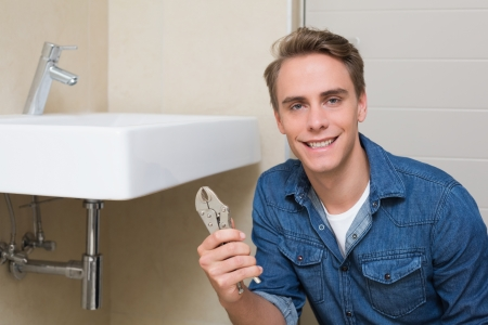 Portrait of a smiling male plumber with wrench by sink in bathroom photo