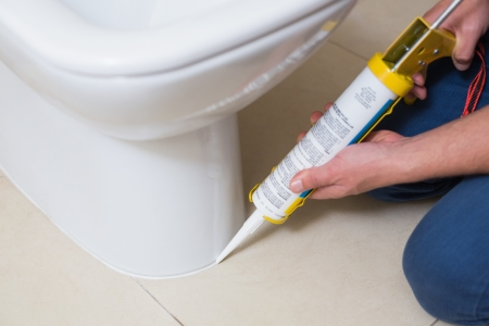 ca�er�as: Primer plano de un inodoro de fijaci�n fontanero en un ba�o con el cartucho de silicona
