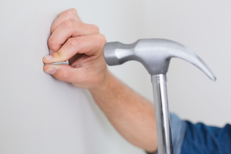 Extreme Close up of a handyman hammering nail in wall photo