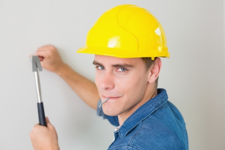 Close up portrait of a young handyman hammering nail in wall photo