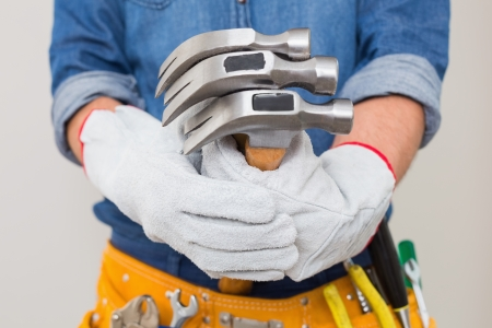 toolbelt: Close up mid section of a handyman holding hammers with toolbelt around waist