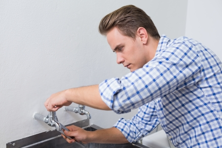 Side view of a serious plumber fixing water tap with pliers photo