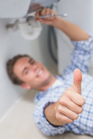 Portrait of a young plumber repairing washbasin drain while gesturing thumbs up in bathroom photo