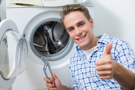 Portrait of a smiling technician repairing washing machine while gesturing thumbs up photo