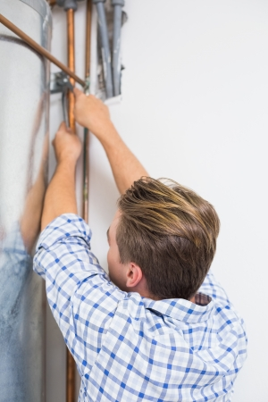Rear view of a young technician servicing an hot water heater pipes photo