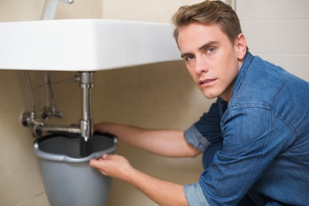 Portrait of handsome plumber repairing the drain of sink in bathroom photo