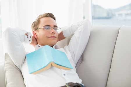 Relaxed thoughtful young man with book lying on sofa in a bright house photo