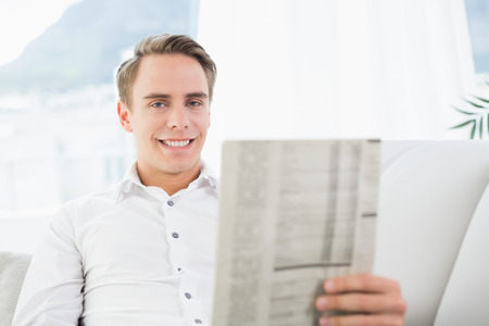 Portrait of a smiling man reading newspaper on sofa in a bright house photo