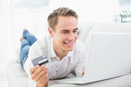 Cheerful casual young man doing online shopping through laptop and credit card on sofa photo