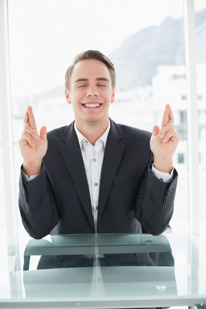 Smiling young businessman with fingers crossed sitting at office desk photo