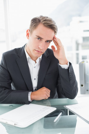 Portrait of a young businessman suffering from headache as he reads documents at office desk photo