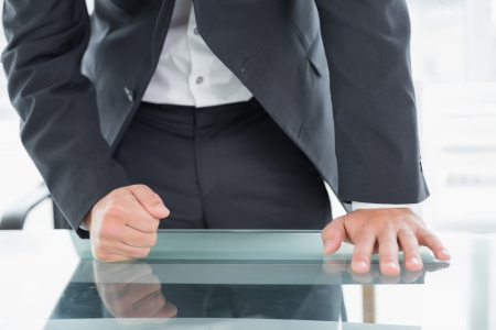 Close up mid section of a well dressed businessman with clenched fist on the desk at office photo