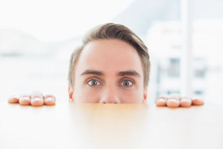 Close up portrait of a young businessman looking over blurred wall at bright office photo