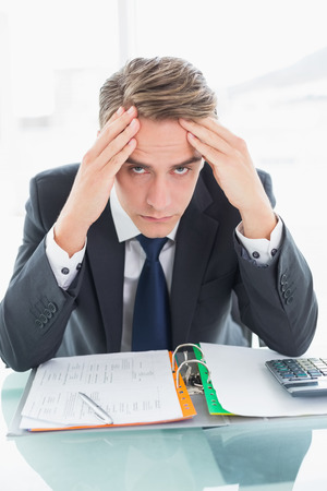 Portrait of a worried young businessman sitting with head in hands at office desk photo